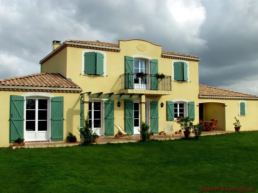 mediterrane Villa mit kräftigen grünen Fensterläden und weissen Fenstern