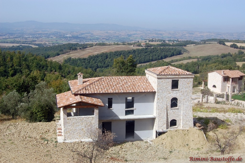 mediterranes Haus mit Gebäudeteilen mit Natursteinfassade