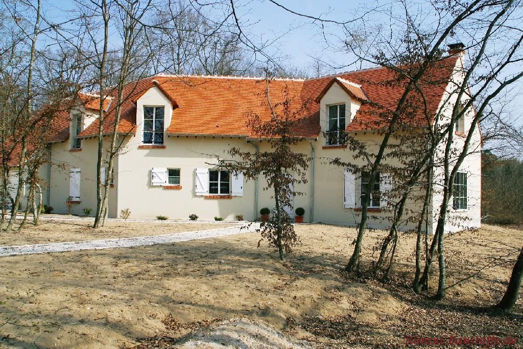 schönes älteres restauriertes Gebäude mit heller Putzfassade und roten Schindeln