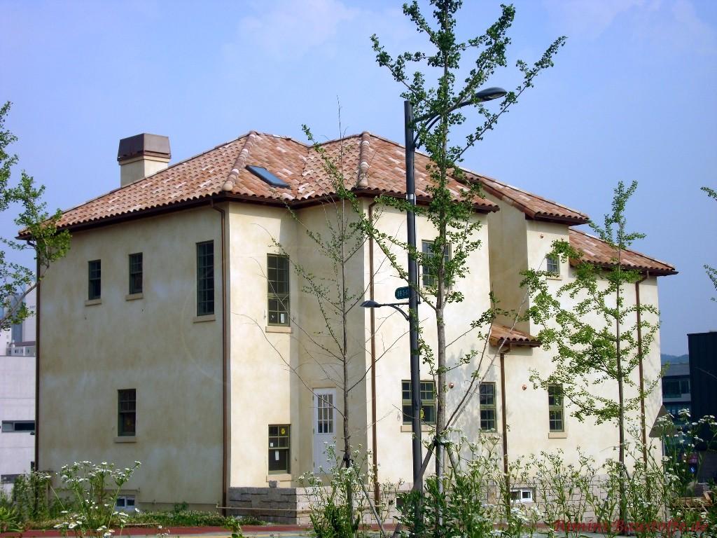 zweigeschossiges Wohnhaus mit changierender gelber Fassade