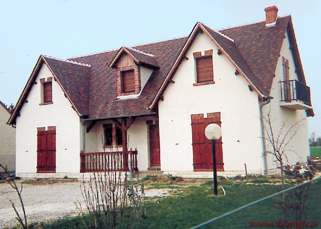 altes Haus mit weisser Putzfassade und Accessoires aus dunklem Holz