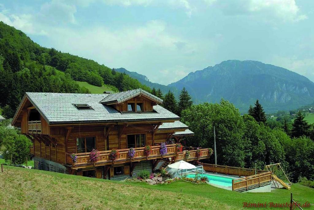 großes Holzhaus mit großem Balkon und Pool in den Bergen
