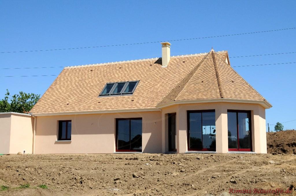 Haus mit großem Erker mit Runddach und dunkelroten bodentiefen Fenstern