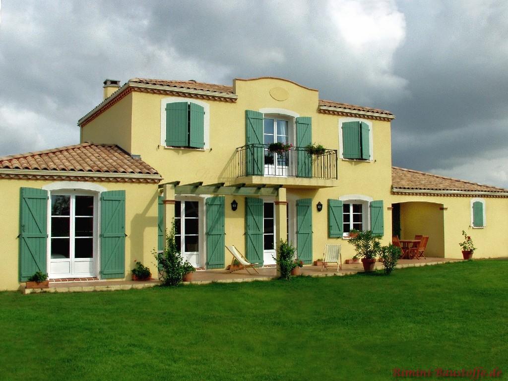 schönes großes Haus im mediterranen Stil mit kräftiger gelber Fassade und grünen Fensterläden