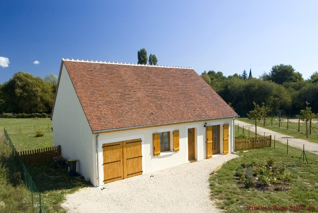 schönes kleines gemütliches Haus mit weisser Putzfassade und hölzernen Fensterläden
