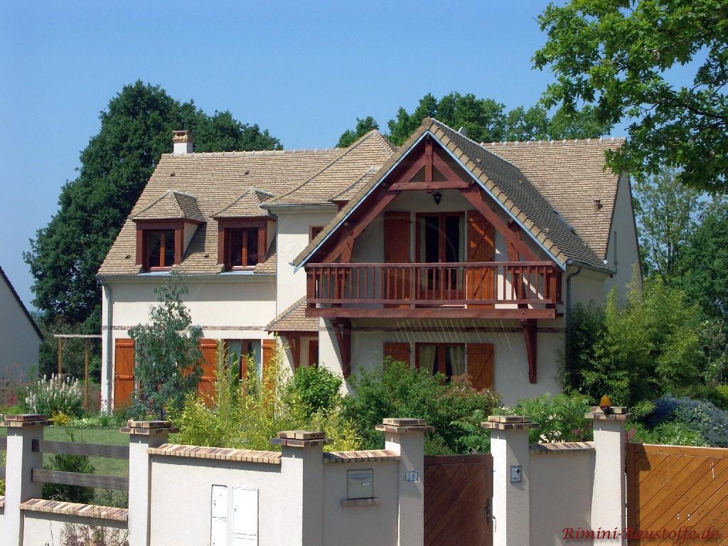 großes Haus mit Balkon und holzfarbenen Fenstern und Fensterläden