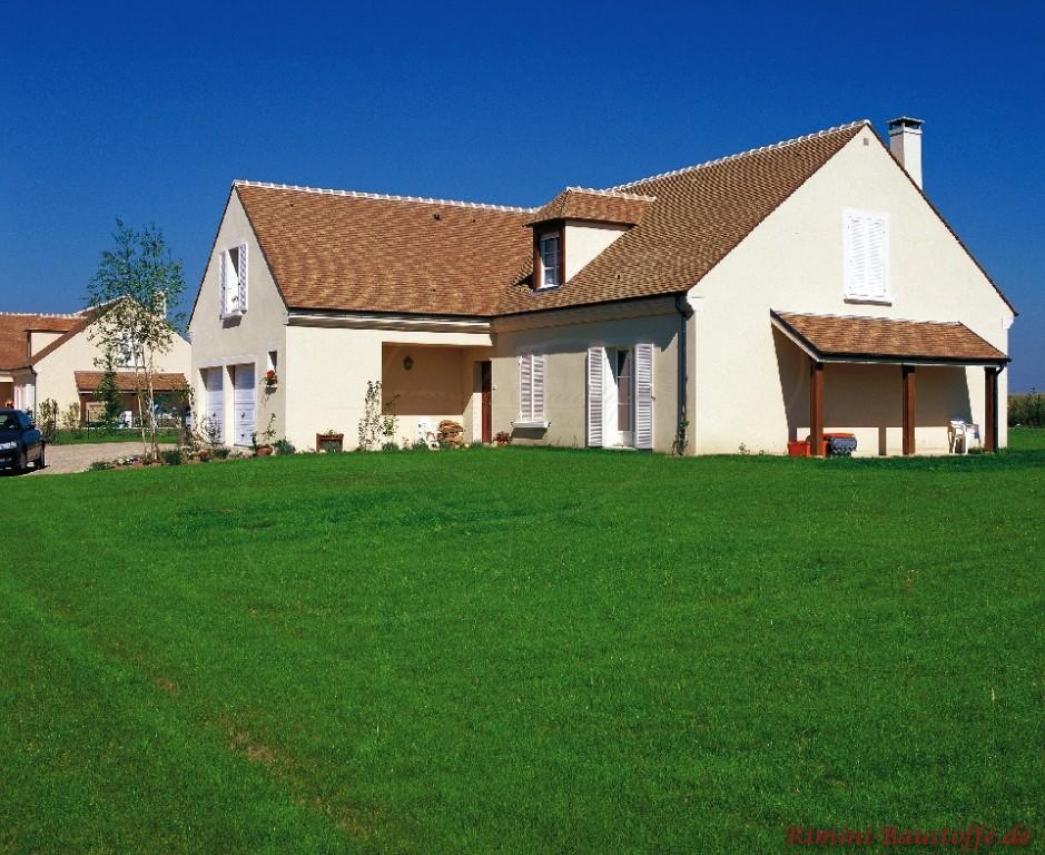 schönes gemütliches kleines Einfamilienhaus mit Satteldach und braunen Schindeln