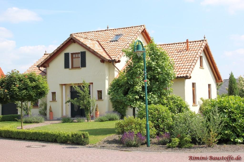 schönes Wohnhaus mit heller gelber Putzfassade und braunen Holzfenstern, passend zum Dach