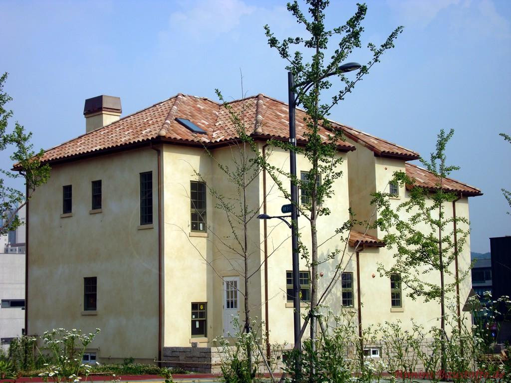 südländisches Haus mit hellgelber Putzfassade und sehr schönem Dach mit changierungen