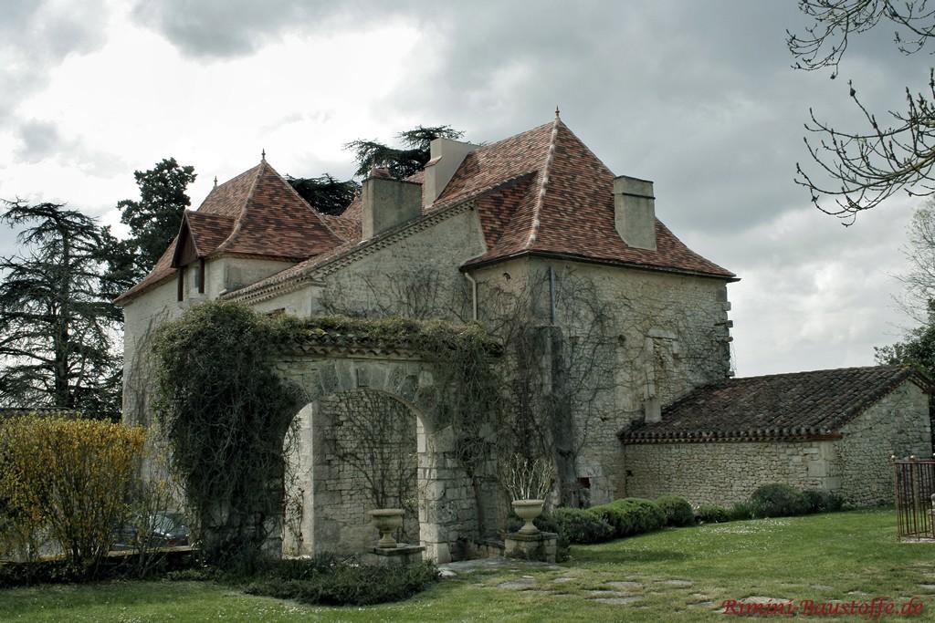 alte Burg mit Natursteinfassade und bunten Schindeln auf dem Dach