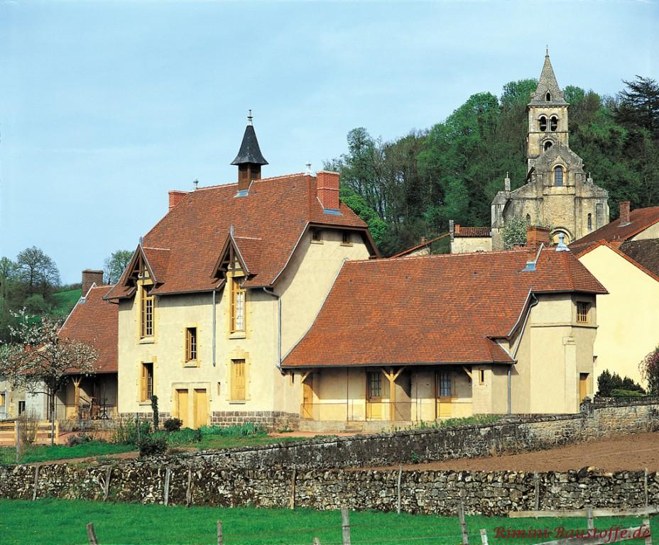 großes, altes Gebäude mit hellen Holzfenstern und dunkelroten Dach
