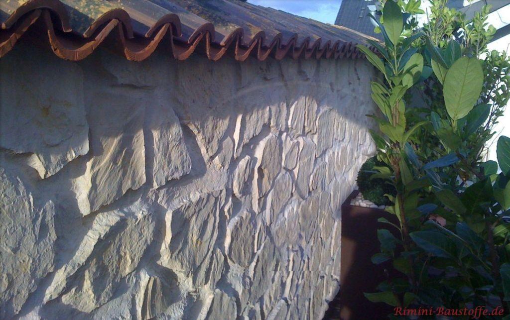 Nahaufnahme einer mediterranen Gartenmauer in antiker Bruchsteinoptik