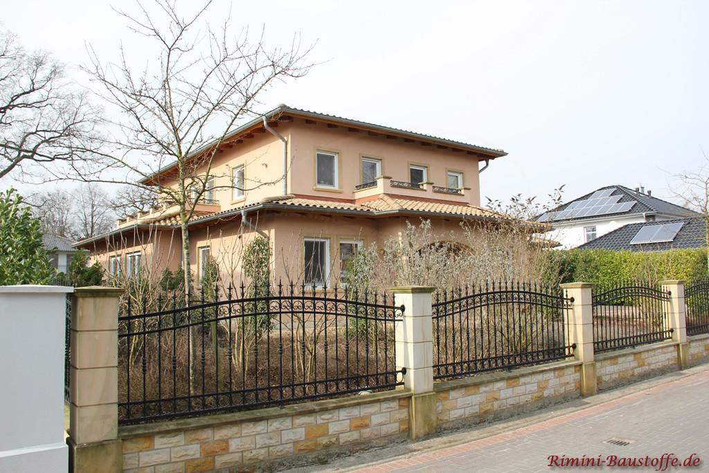 mediterranes Wohnhaus mit farbigen Faschen zu weißen Fenstern