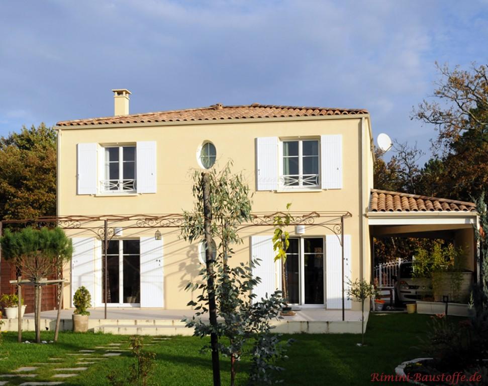 mediterrane Villa mit gelber Fassade und weissen Fensterlaeden