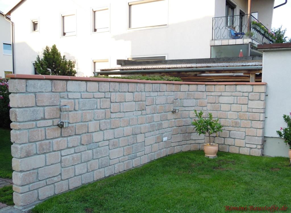 Gartenmauer aus grauem Naturstein mit rötlichen Nuancen
