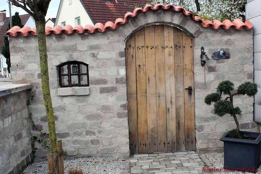 graue Gartenmauer mit Holztür und mit Halbschalen gedeckt