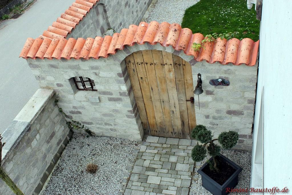 Aufsicht auf eine mediterrane graue Gartenmauer mit Halbschalen abgedeckt