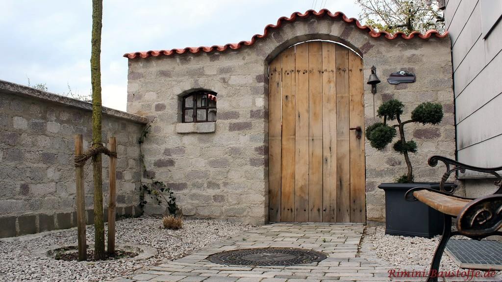 geschwungene Gartenmauer mit schöner Holztür und kleinem Sprossenfenster