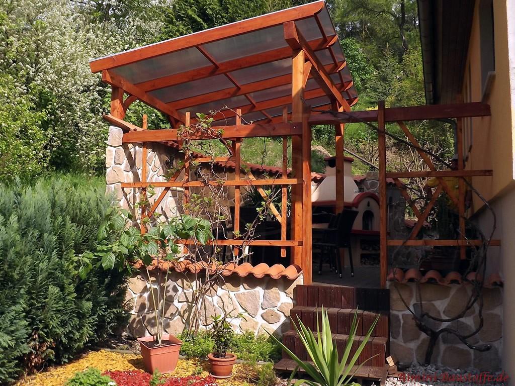überdachte Terrasse mit mediterraner Gartenmauer