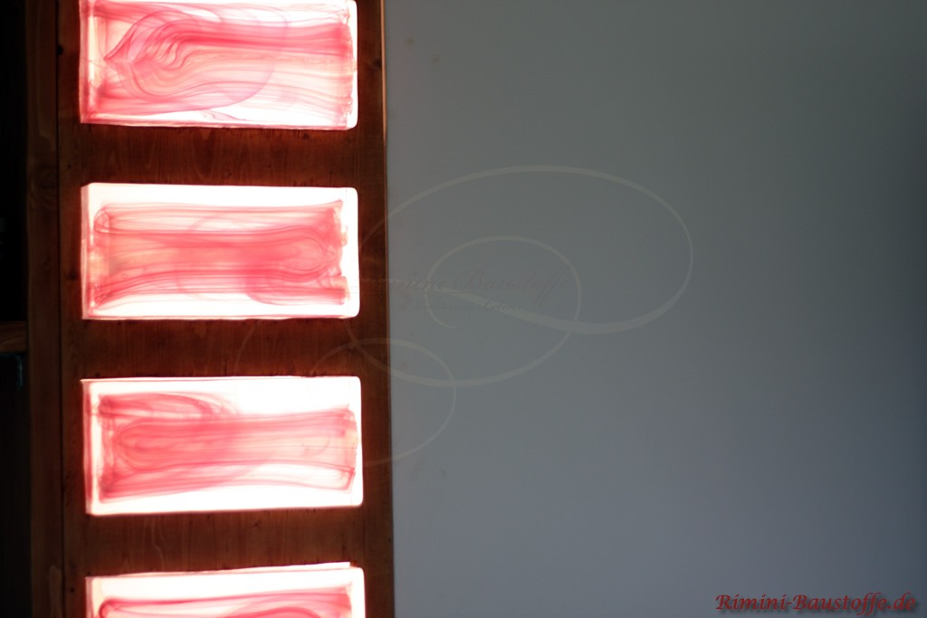 Rosane Galselemente eingelassen in einen dunklen Holzbalken mit Beleuchtung