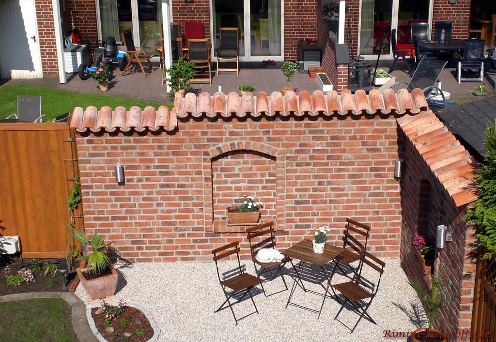 Sitzecke im Garten im mediterranen Stil mit Klinkermauer und Mönch Nonne Abdeckung