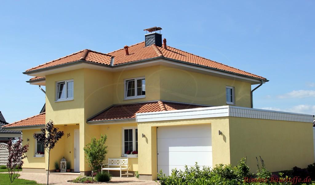schönes großes Wohnhaus im mediterranen Stil mit gelber Putzfassade und rotem Dach