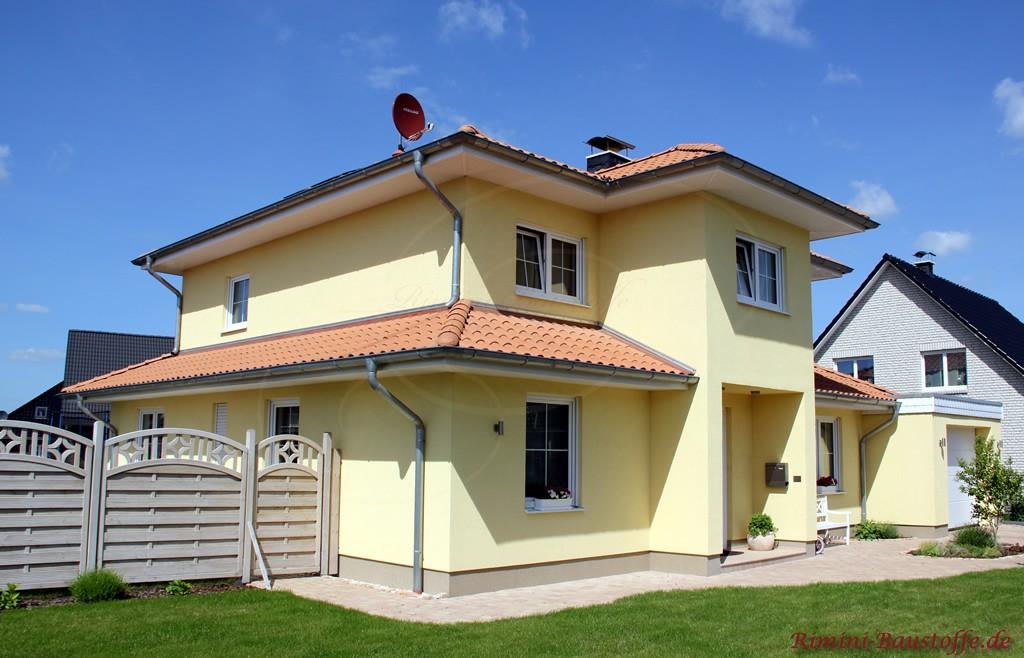 schönes abgestimmtes Wohnhaus mit gelber Fassade und rotem Dach