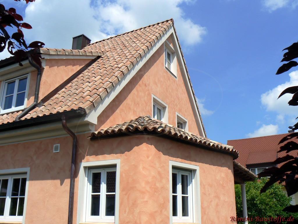 schöner romanischer Dachziegel passend zur hellroten Putzfassade