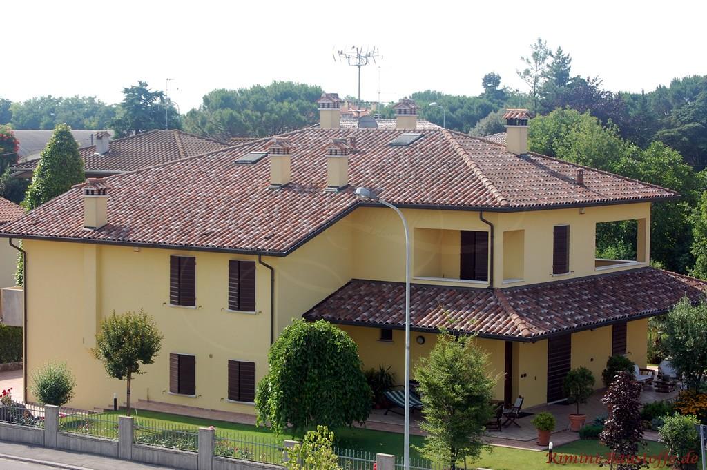 große mediterrane Villa mit gelber Putzfassade und rot geflammtem Dach