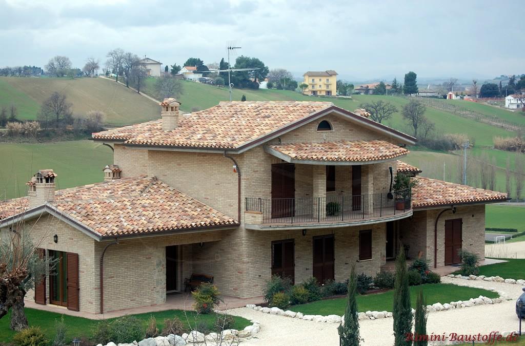 große südländische Villa mit heller Klinkerfassade und dunklen Fensterläden