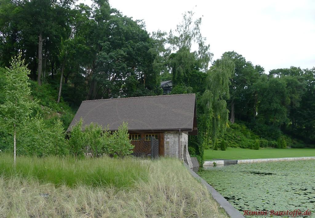 Haus am See mit grauer Natursteinfassade und Holzfenstern