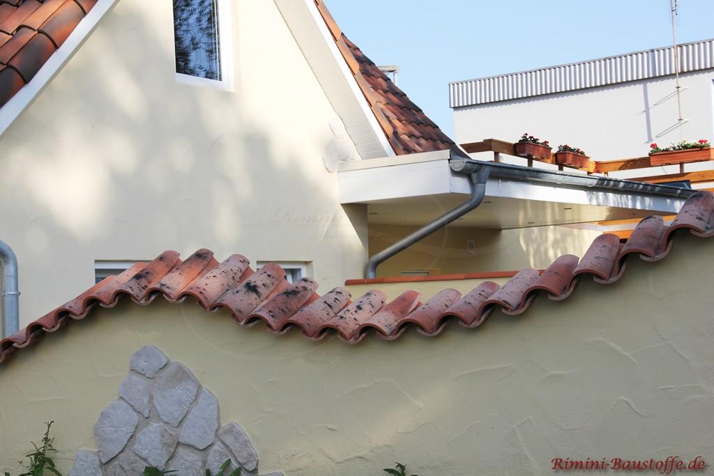 geschwungene Gartenmauer im mediterranen Stil mit Halbschalen gedeckt