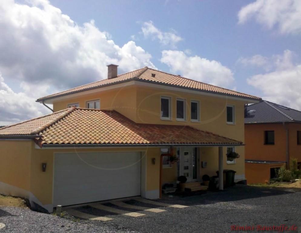 mediterranes Wohnhaus mit kräftiger gelber Putzfassade und einem roten Dachziegel