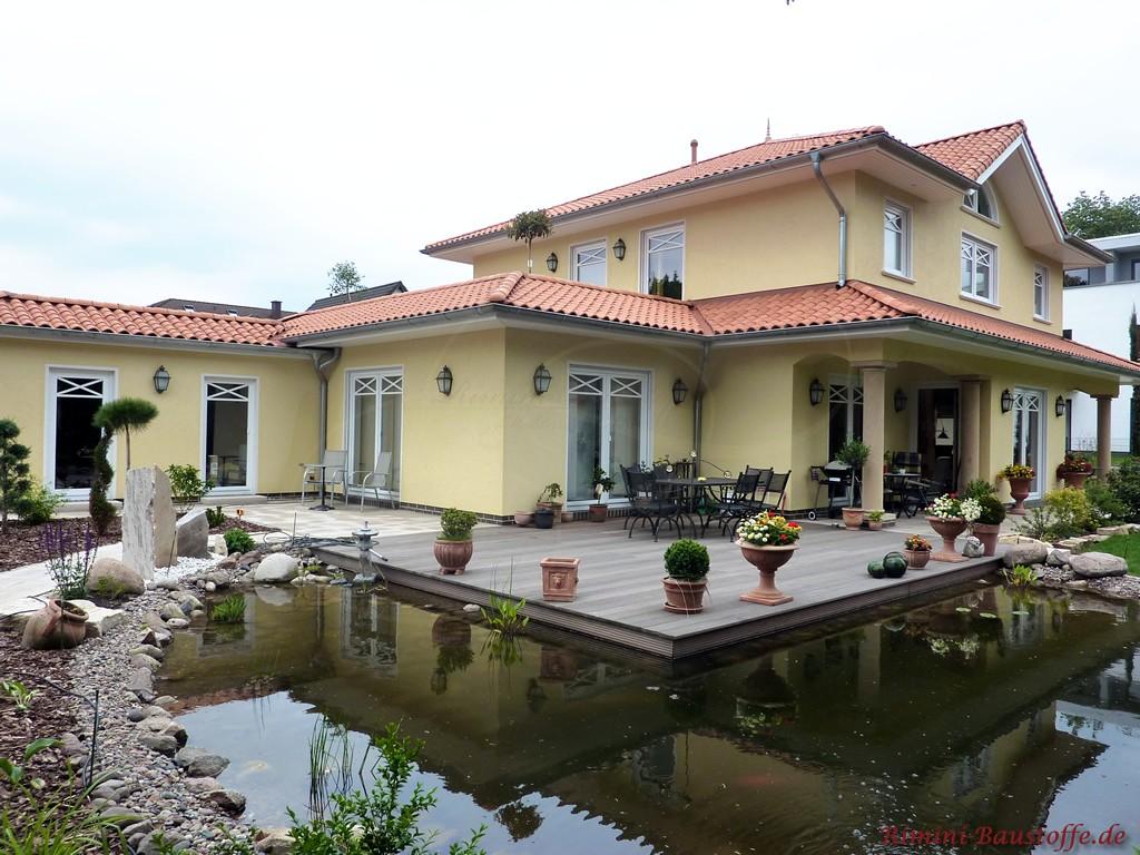 große mediterrane Villa mit überdachter Terrasse und angrenzendem Teich