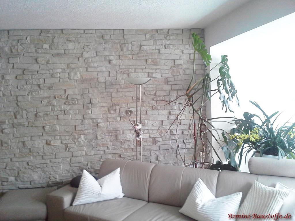 Wohnzimmerwand in heller Natursteinoptik mit hellen Möbeln