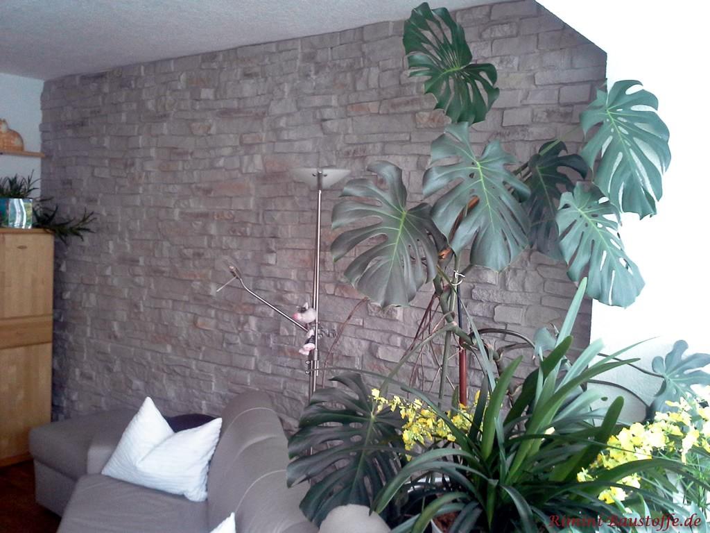 Wohnzimmerwand in grauer Natursteinoptik passend zu den hellen Möbeln