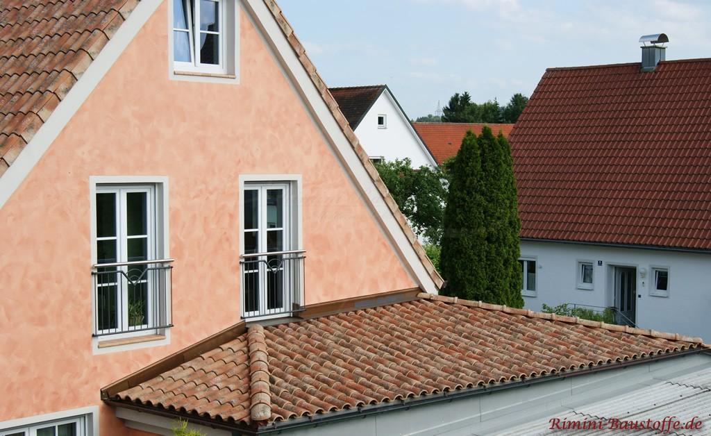 farbige Putzfassade mit sehr schönem Wischmuster und passend gewähltem Dachziegel