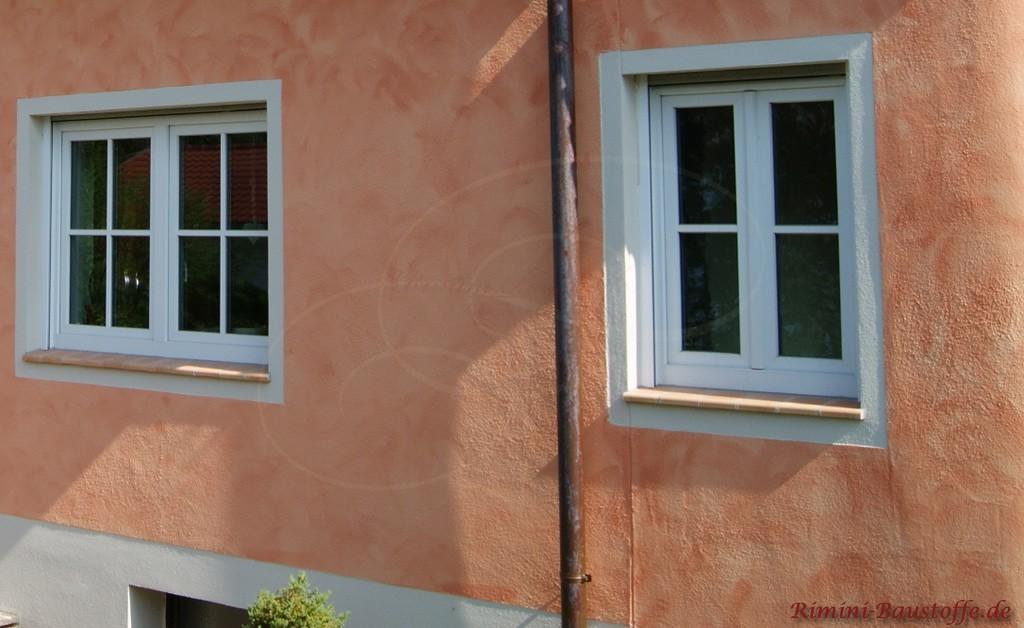 farbige Putzfassade und weisse Fenster mit passenden Fensterbaenken aus Ton