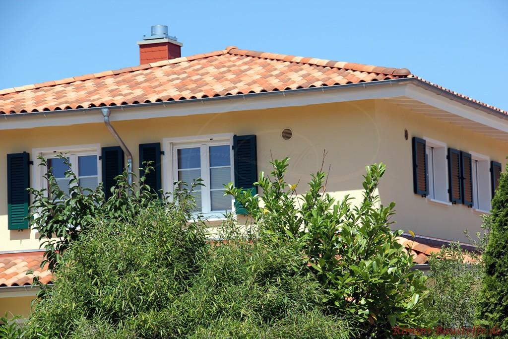 mediterrane Villa mit schöner gelber Putzfassade und grünen Fensterläden
