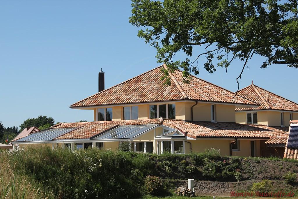 große mediterrane Villa mit vielen Fenstern und einem Wintergarten