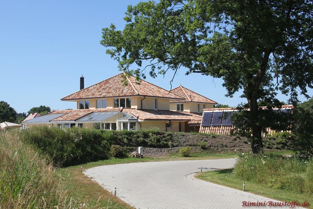große Villa im südländischen Stil mit Dachziegeln in alter Herbstlaubfarbe