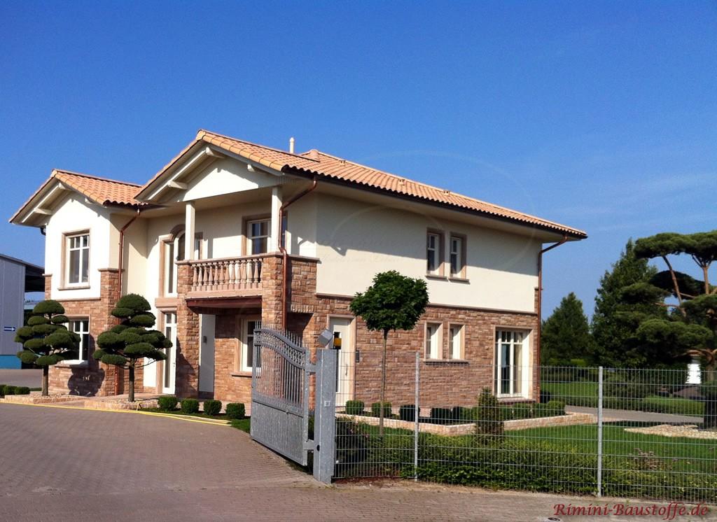 Doppelgeschossiges Haus mit halbhoher Natursteinfassade und hellem Dach