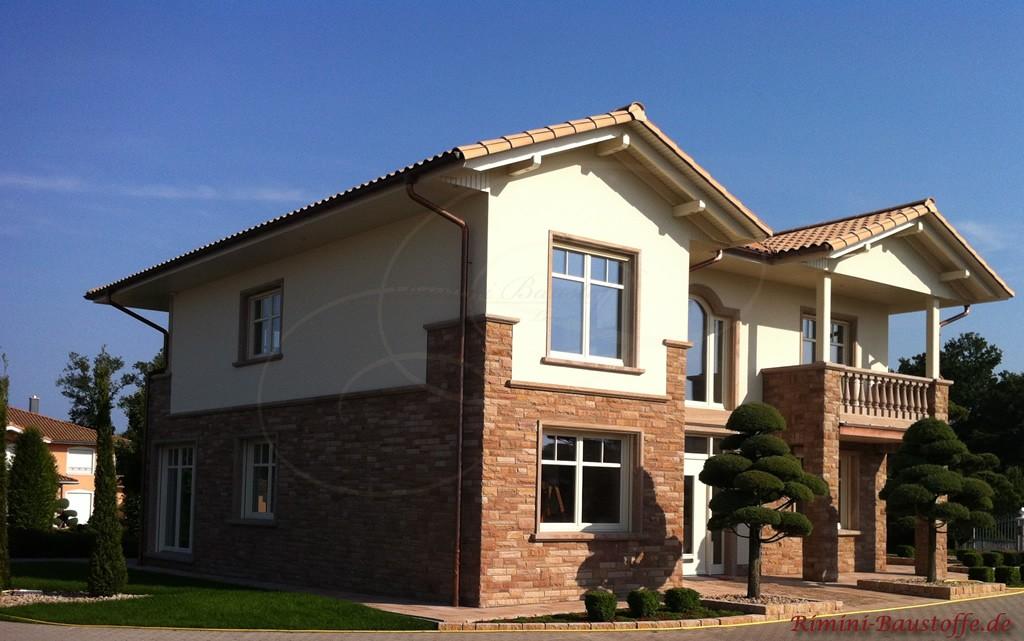 großes Bürogebäude im Stil eines Einfamilienhauses. Helle Putzfassade, helles Dach und eine Natursteinsockel