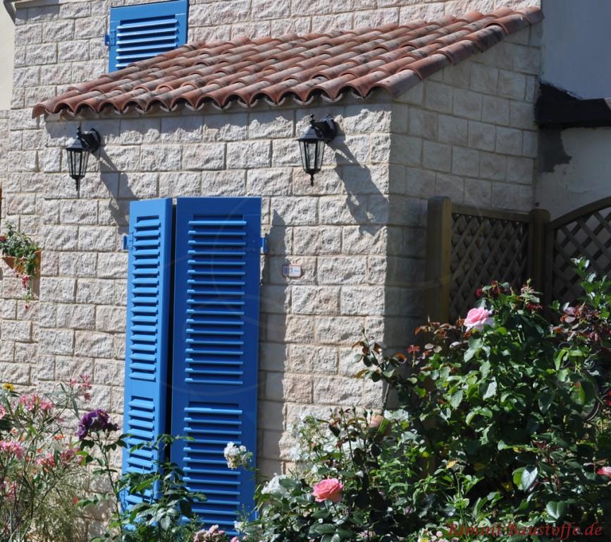 Erker in heller Natursteinoptik mit kräftigen blauen Fensterläden