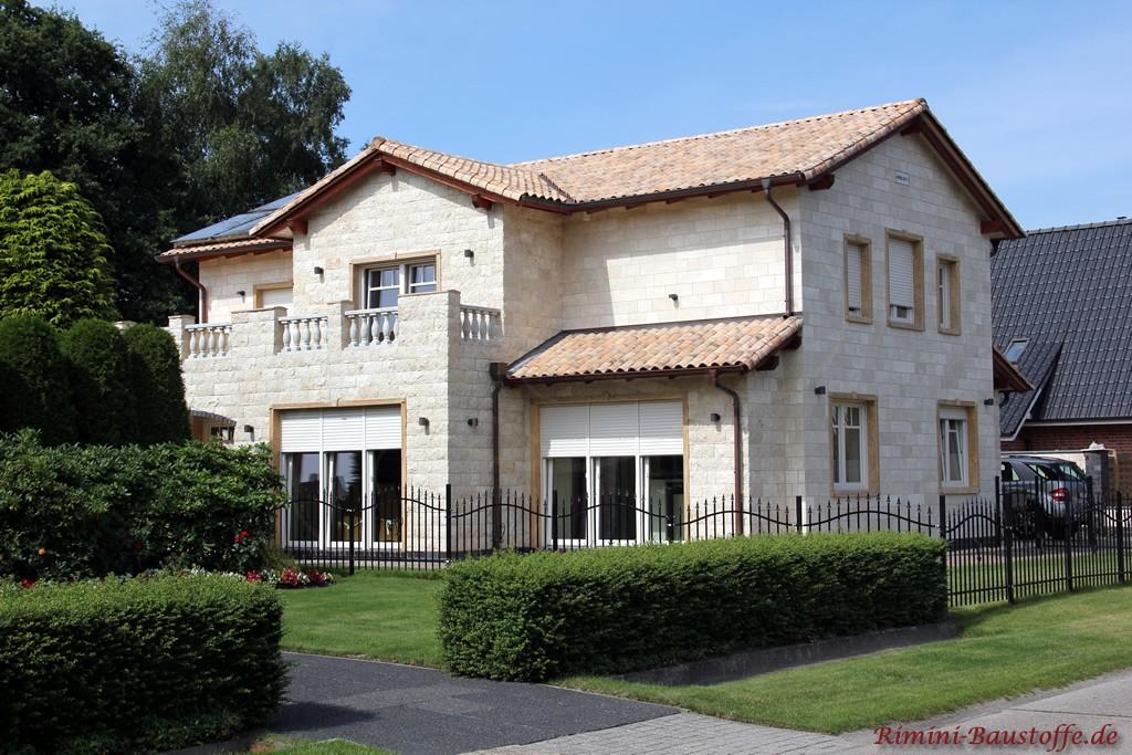Einfamilienhaus mit Fassade in heller Sandsteinoptik und hellem Dachziegel