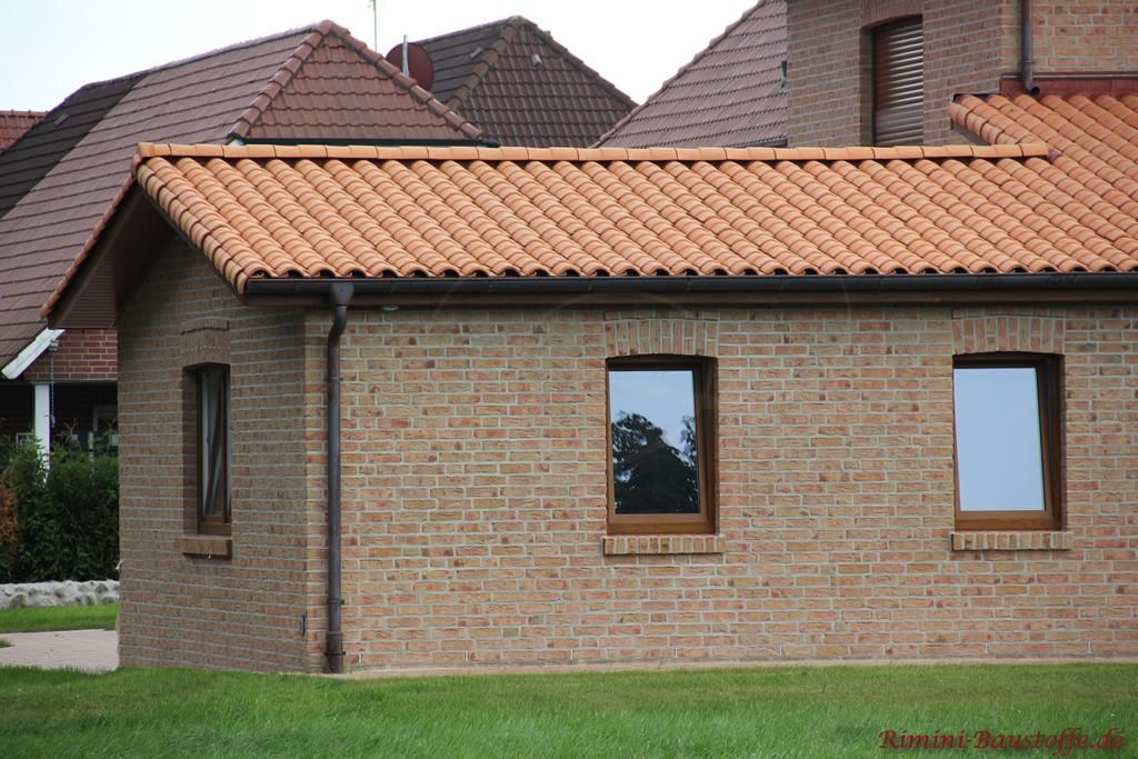 braune Fenster zu einem hellbraunen Klinker und einem rosefarbenen Dach