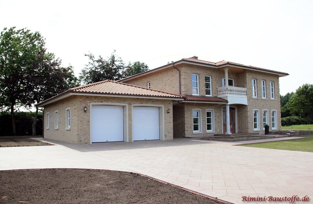 brauner Dachziegel zu einer hellen Klinkerfassade mit weissen Fenstern