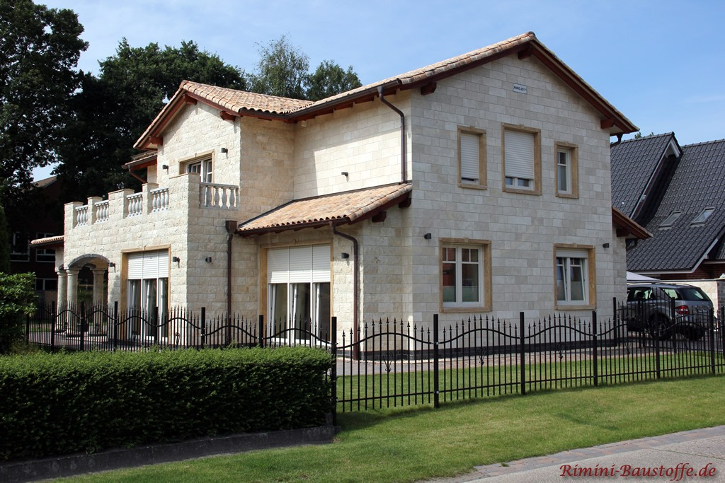 Familienvilla mit Fassade in heller Sandsteinoptik und aufwendiger Beleuchtung