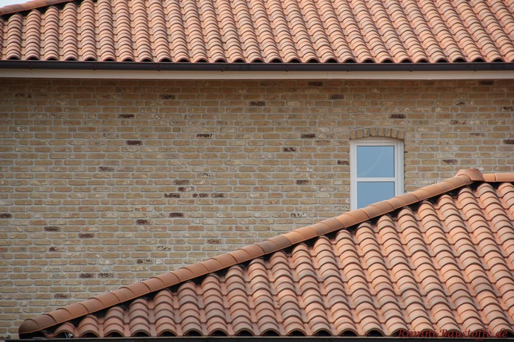 brauner mediterraner Dachziegel zu einer hellen Klinkerfassade