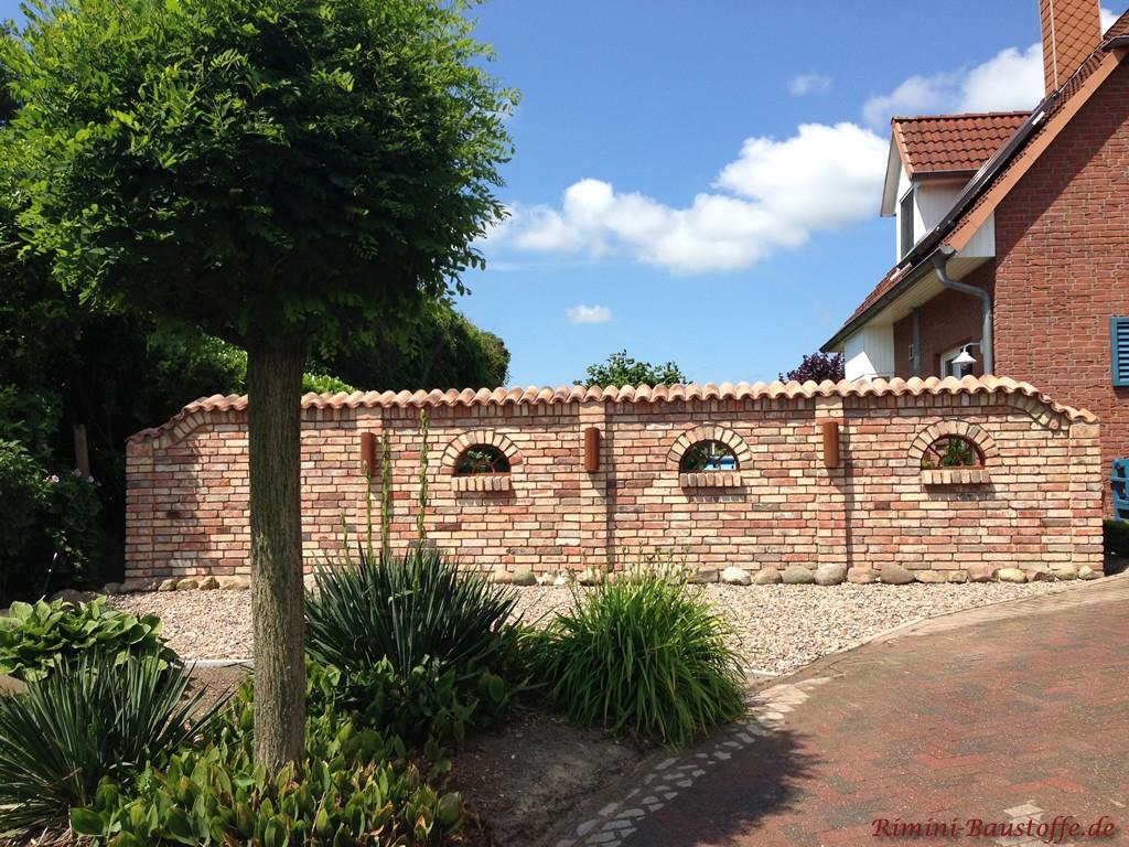 schöne antik wirkende Gartenmauer mit halbrunden Fenstern